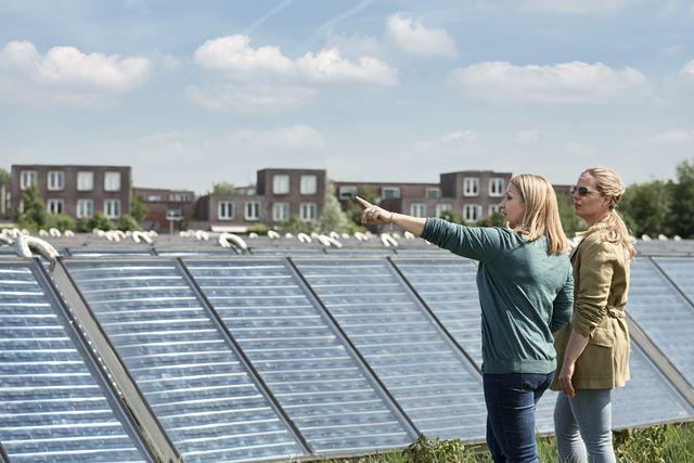 Femmes debout à côté de panneaux solaires dans un quartier résidentiel