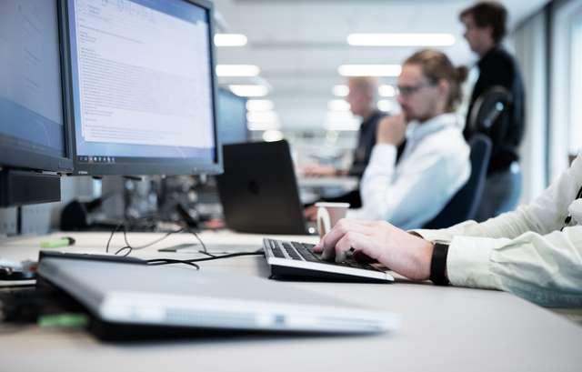 Homme qui travaille sur son ordinateur en open space