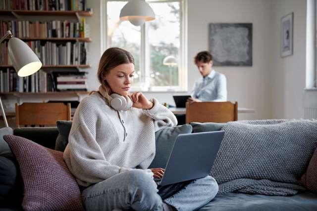 Homme et femme derrière leur ordinateur dans le salon